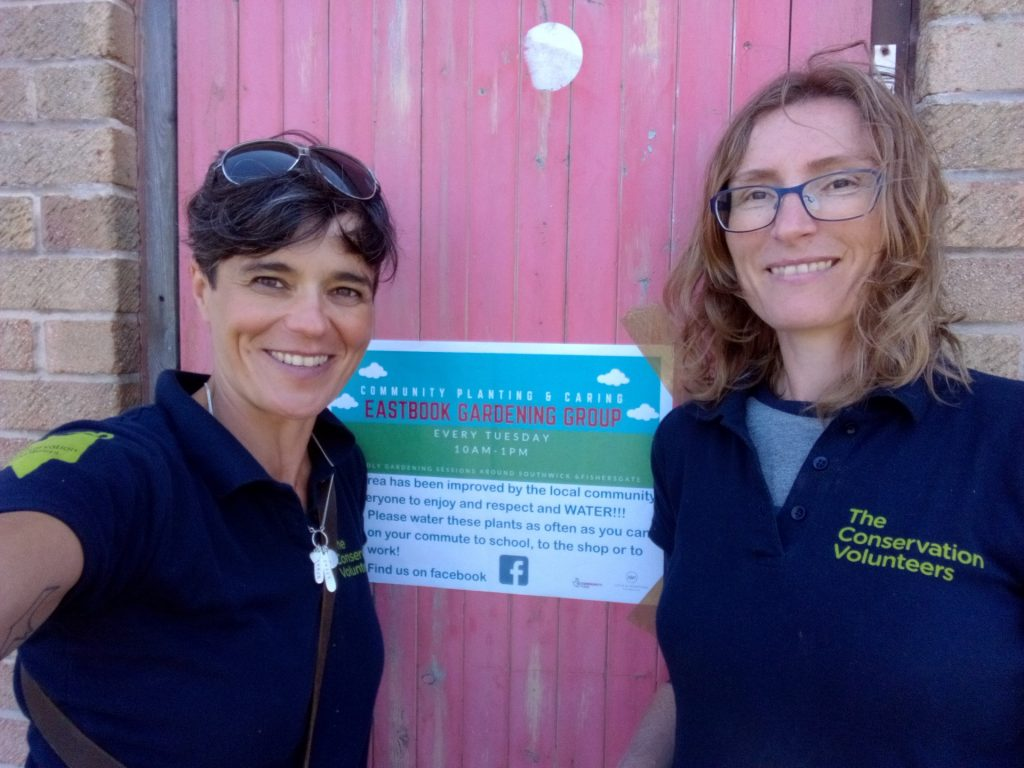 TCV team smiling next to a sign for local gardening group