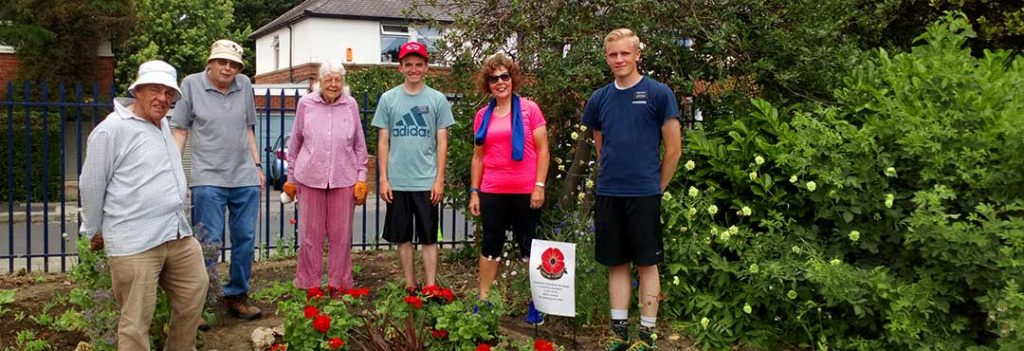 Group of volunteers with a patch of poppies
